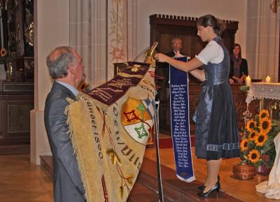 Festabend TSV Velden - Kristina Rostin hängt das Ehrenband an Vereinsfahne